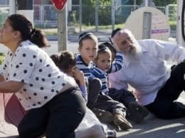 Família judia tenta se proteger atrás de um carro após alerta de ataque na cidade de Kiryat Malachai, no sul de Israel (Jim Hollander/Efe)