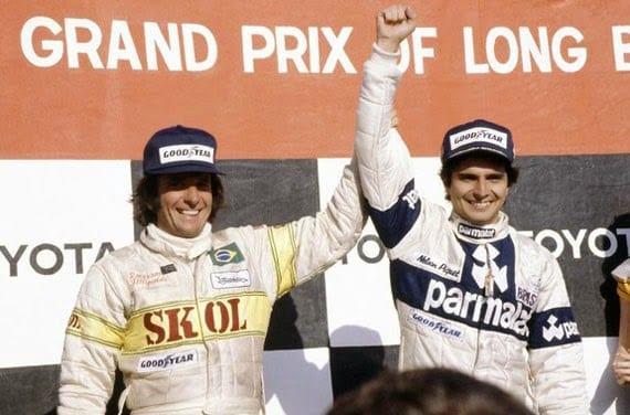 """Emerson ergue o braço e """"passa o cetro"""" a Nelson Piquet, que vencia o primeiro GP da carreira, em Long Beach (EUA), 1980 (Rodrigo Mattar)"""