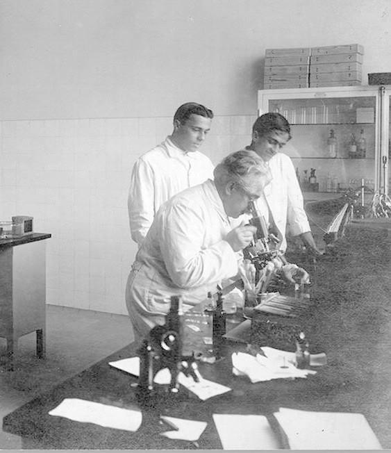 CÁTEDRA - Oswaldo Cruz ministra aula no laboratório de Manguinhos, observado por seu filho Bento Oswaldo Cruz e por Burle de Figueiredo. Foto: Arquivo e Documentação da Casa de Oswaldo Cruz (Fiocruz).