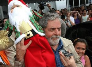 MARKETING ELEITORAL - O ex- presidente Luiz Inácio Lula da Silva carrega um Papai Noel que recebeu de presente durante visita aos desabrigados pelas enchentes em Blumenau - SC no dia 12 de dezembro de 2008.
