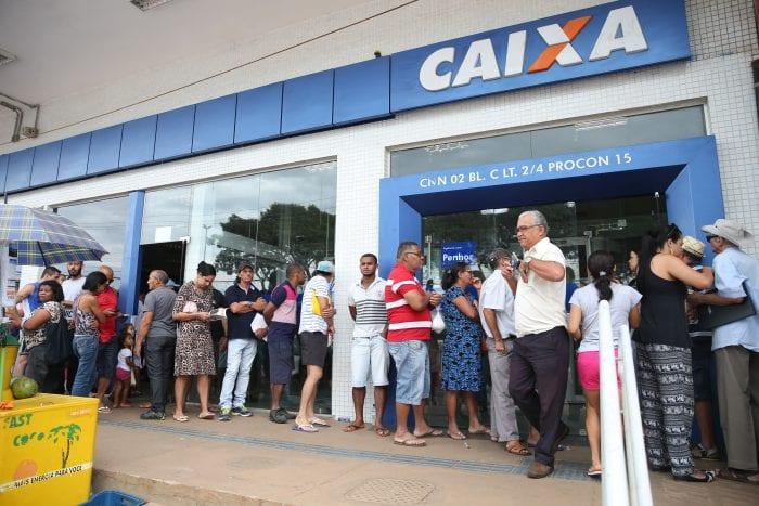 Pessoas em fila para sacar benefícios sociais - foto de Antonio Cruz/Agência Brasil