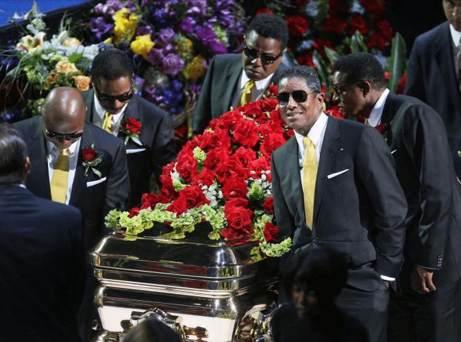 Caixão de Michael Jackson é carregado por seus irmãos e ex-parceiros de banda juvenil em cerimônia de despedida no Staples Center, em Los Angeles (2009) - foto de MARIO ANZUONI / UNITED PRESS INTERNATIONAL