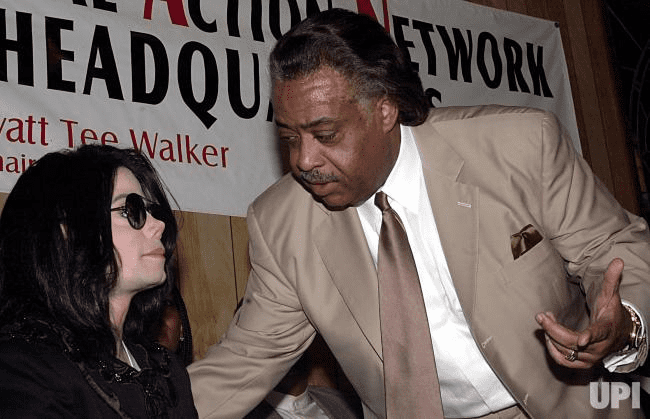 Michael Jackson discursa contra Tommy Mottola, então presidente da gravadora Sony, na companhia de Al Sharpton, em Nova York (2002) - foto de EZIO PETERSEN / UNITED PRESS INTERNATIONAL