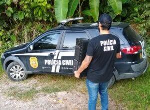 Agente com computador apreendido em casa de suspeito - foto da Polícia Civil