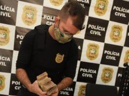 Policial civil contabilizando dinheiro apreendido - foto da Polícia Civil